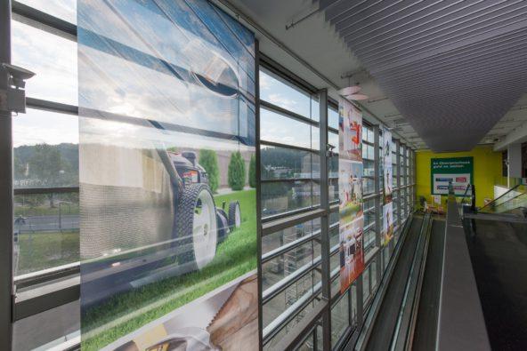 Textilbanner hinter Glasfassade inklusive Abhängevorrichtung /